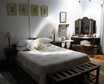 Large room featuring a double and single beds, antique furniture, two-seater couch, bath and shower.
