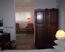 This room features a private entrance, lounge and verandah,  large shower, antique furniture and double and single beds.
