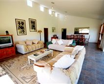 The Farmhouse which sleeps 10 has a elegantly furnished spacious lounge/dining room which has a TV. Sliding doors on both sides provides vistas of the nearby dam and mountains and open up onto the patio which is perfect for lazy afternoon braais.