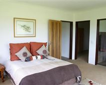 The main bedroom has a bathroom ensuite with jacuzzi bath and sliding doors onto a patio with a beautiful berg view.