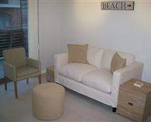 Relax in the living room which includes a TV, sofa, chairs, magazines and access onto a balcony.