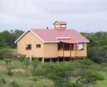 Cottage with two bedrooms, a bathroom, full kitchen, dining and lounge area, verandah, fireplace, and braai area.