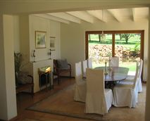 Charming eight-seater dining room with a fireplace, overlooking the Magaliesberg Mountains and Valley.