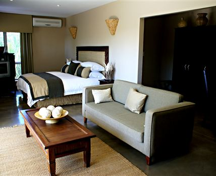 A luxury en-suite room with a king-size bed, a balcony and a river view.